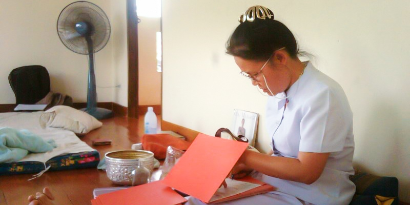 Teacher Dot Po signing Thai Massage Completion certificates at the Sunshine Massage School