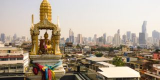 Spirit house and Bangkok's skyline in the background - view from a rooftop bar