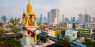Spirit house and Bangkok's skyline in the background - view from